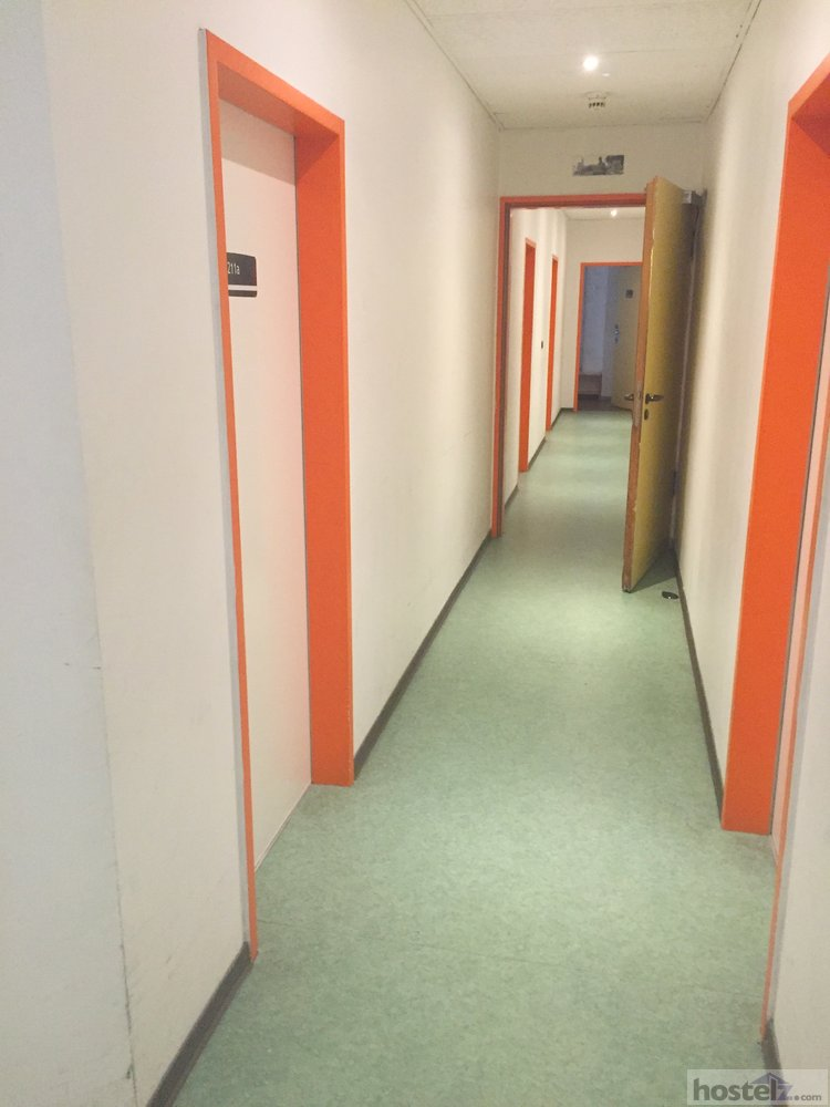 A hallway with doors to rooms on one of the floors